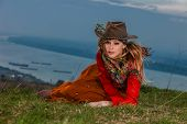 young blond woman in autumn fashion clothes, hat, red leather jacket, cashmere scarf and brown pants outdoor shot blue sky and river in background