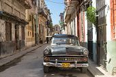 HAVANA-OCTOBER 17:Old american car in a street sidelined with decaying buildings October 17,2013 in Havana.These cars,still in use after many decades,have become a worldwide known symbol of Havana