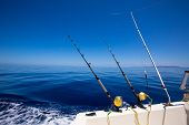Ibiza fishing boat trolling with rods and reels in blue Mediterranean sea Balearic