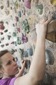 Determined young woman climbing up a climbing wall