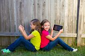 Twin sister girls playing with tablet pc sitting on backyard lawn fence leaning on her back