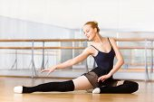 stock photo of ballet barre  - Bending ballet dancer stretches herself on the floor in the classroom - JPG