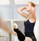 stock photo of ballet barre  - Female ballet dancer stretches herself near barre and mirrors in the classroom - JPG