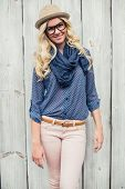 Cheerful fashionable blonde posing outdoors on wooden background