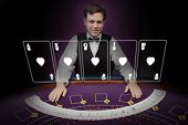 Picture of croupier standing behind holographic cards behind purple table in dark room