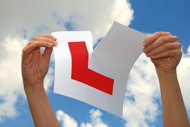 stock photo of driving school  - Woman ripping a car L plate held towards the sky after succeeding in passing driving test - JPG