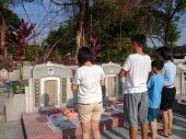 PETALING JAYA MARCH 30: Family members pray at their ancestors graves on Tomb Sweeping Day or the Qi