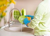Woman Washing Dishes. Kitchen. Dishwashing. Woman doing housework at home