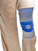 Sports Knee Brace - A Stabilizing Silicone Blue And Gray Medical Sports Knee Brace Worn Over Sweatpa