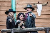 stock photo of gallows  - Old west trio points guns at you - JPG