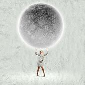 Conceptual image of businesswoman holding huge moon above head