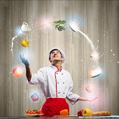 Young man at kitchen juggling with ingredients