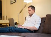 Young man with fray hair with laptop on sofa in home interior