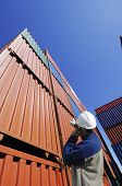 port and dock worker directing stacks of cargo containers inside port
