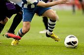 Legs of two soccer players vie on a match
