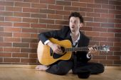 Businessman Sits With A Guitar On The Floor And Sings