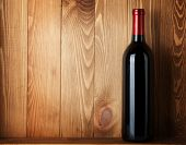 Red wine bottle over wooden background with copy space