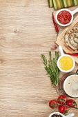 Grilled sausages with ketchup, mustard and mug of beer. Over wooden table background with copy space
