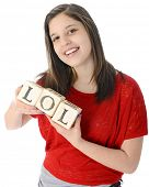 A pretty young teen happily holding rustic alphabet blocks with her text-message abbreviation: LOL (meaning laughing out loud).  On a white background.