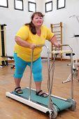 fitness - overweight woman running on trainer treadmill