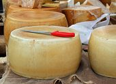 stock photo of milkman  - excellent yellow cheese on sale from milkman into a village fair - JPG