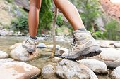 Hiking shoes on hiker outdoors walking crossing river creek. Woman on hike trekking in nature. Close