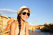 Backpacking women traveler on travel in Florence wearing sunglasses smiling happy by Ponte Vecchio d