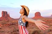 Cowgirl - woman happy and free in Monument Valley wearing cowboy hat with arms outstretched in freedom concept. Beautiful smiling multiracial young woman outdoors, Arizona Utah, USA.