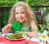 Child at cafe. Girl at restaurant eating salad