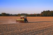 picture of plowing  - Tractor plowing on dry field in spring before sunset - JPG