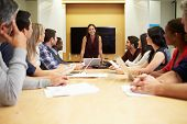 Female Boss Addressing Meeting Around Boardroom Table