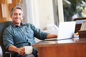 image of mature adult  - Mature Hispanic Man Using Laptop On Desk At Home - JPG