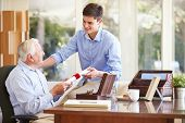 stock photo of keepsake  - Grandfather Showing Document To Teenage Grandson - JPG