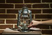 Hand lights a kerosene lamp on brick wall background