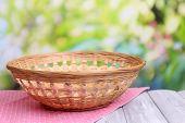 Empty wicker basket on wooden table, on bright background