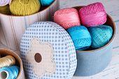 Decorative boxes with colorful skeins of thread on wooden background