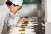 Side view of a concentrated female chef garnishing food in the kitchen