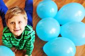 Boy Laying On The Wooden Floor With Blue Balloons