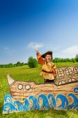 pic of pirate sword  - Excited boy dressed in pirate costume laughing and holding sword on ship made of cardboard - JPG