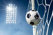 Soccer Ball In The Goal Net With Stadium Lights In The Background