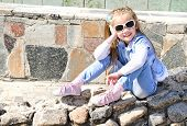 Adorable Little Girl Sitting On Stones