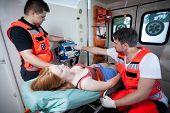 Paramedics Applying First Aid In Ambulance