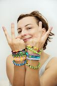 Smiling Young Woman With Colorful Rubber Bracelets On Her Hands