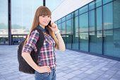 Teenage Girl Talking By Phone Standing On Street Against School Building