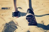 Girl Feet In Sneakers Go Away On The Sand. Ton