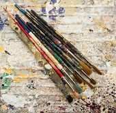 paint brushes on grungy paint background