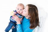 Beautiful Young Mother Kissing Her Little Baby Boy Both Wearing Blue Knitted Sweaters, On White Back