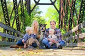 stock photo of puppies mother dog  - A portrait of a happy family of four people including mother father young child and baby brother and their pet German Shepherd Mix dog are sitting on an old bridge with the fallen leaves in Autumn - JPG