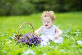 Beautifu Baby Girl With Blond Curly Hair Wearing A White Dress Playing With A Flower Basket