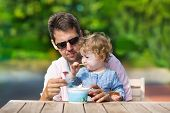 Young Handsome Father And His Little Baby Daughter Enjoying Ice Cream In The Garden